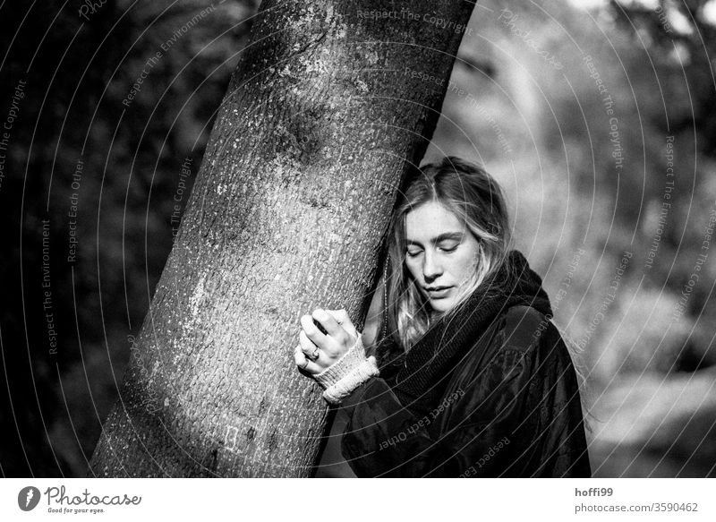 the young woman leans against a tree and looks down thoughtfully Young woman Meditative Blonde melancholy Long-haired blonde hair long hair Woman