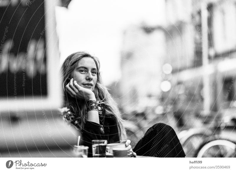 the young woman looks relaxed and joyful to escape the coming Young woman Face of a woman blurred background 18 - 30 years Adults Strand of hair Human being