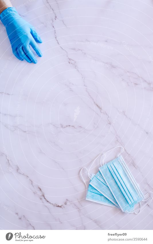 Flat lay of a hand on medical gloves and some surgical masks against a marble background health breath nursery medicine flat lay flatlay copy space copyspace