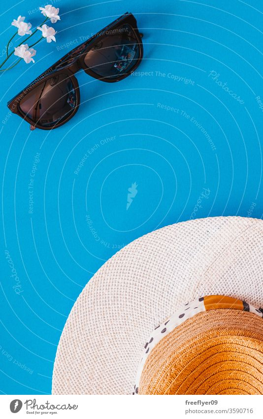 Flat lay of objects related to summer and spring against a blue background sunglasses hat flat lay flatlay copy space copyspace still still life from above