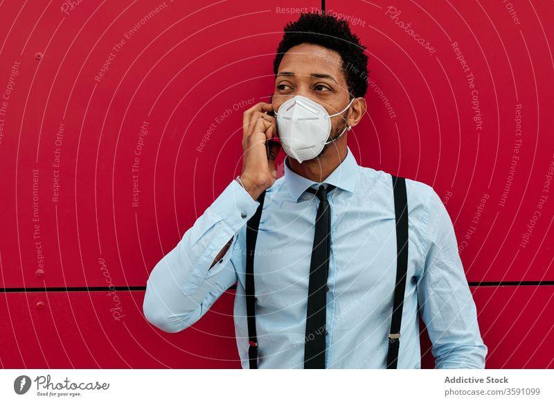 Serious ethnic businessman in respirator talking on smartphone on street phone call mask protect city pandemic infection virus entrepreneur coronavirus epidemic