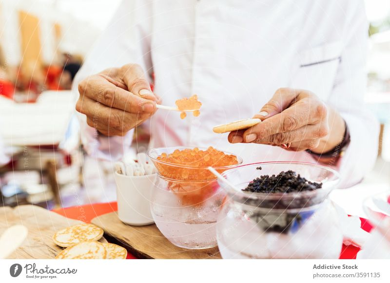 Man serving snack with caviar food serve flatbread starter appetizer buffet put person tradition yummy tasty delicious meal dish gourmet service treat cuisine