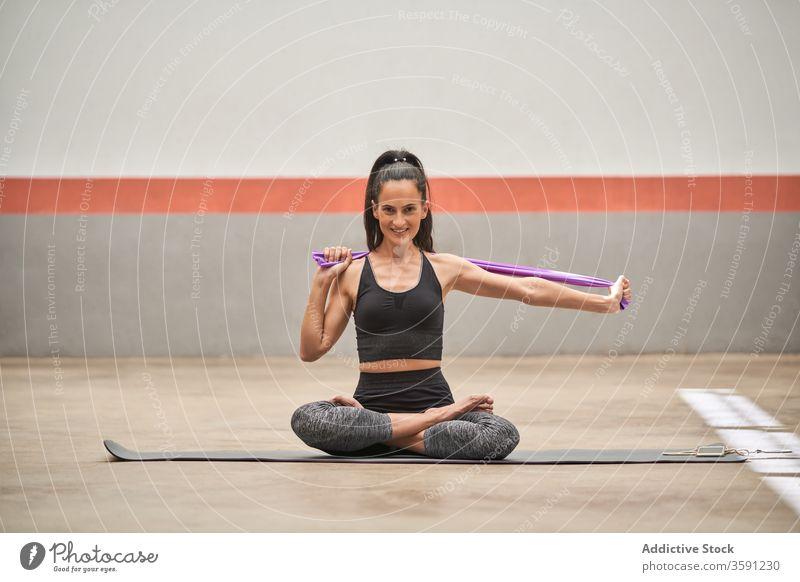 Smiling woman in lotus pose in gym yoga meditate tranquil mat padmasana sportswear female healthy wellness calm resist elastic band equipment sit relax harmony