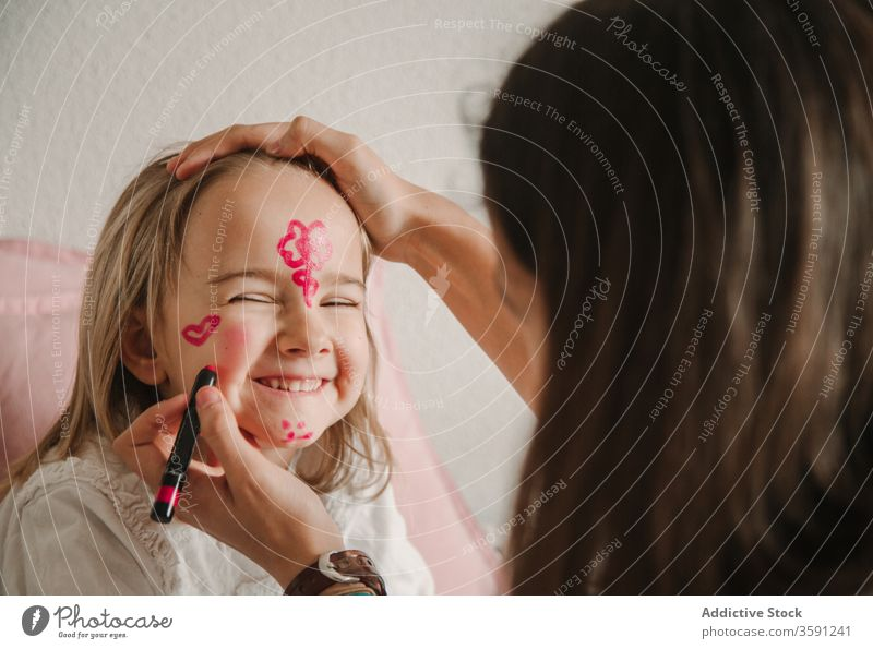 Cute girl with painted face sister having fun weekend play pastime color home sibling together playful relationship kid teen little childhood cute teenage