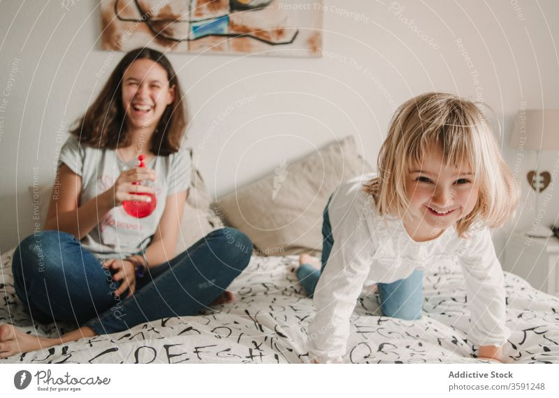 Playful sisters having fun with pulverizer at home play sprayer water weekend together cheerful playful kid girl bed teenage little joy childhood sibling sit