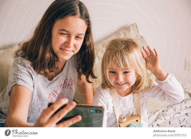 Cheerful sisters taking selfie on smartphone at home grimace girl sibling using having fun gesture teenage little peace charming content camera device gadget