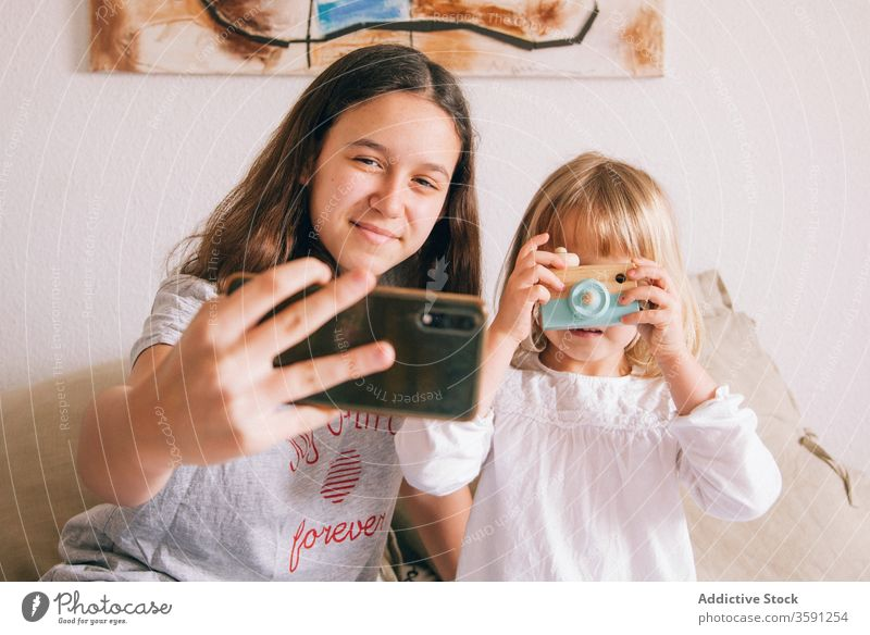 Content sisters taking selfie on mobile phone smartphone teenage little girl using charming content having fun toy camera device gadget kid bed sit adorable