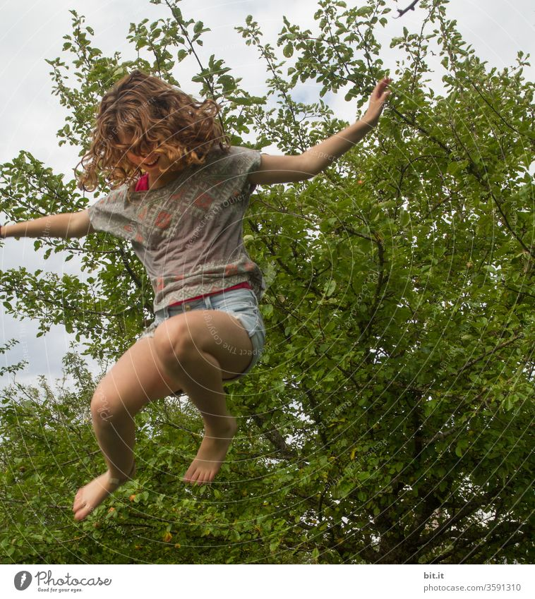 Curly, spirited joker jumps on trampoline in the garden. Girl flies, jumps, jumps lively, happy, wild, crazy up Sport, light-heartedness, exercise and fitness against stress, problems, fear at school and at home.