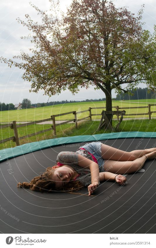 Tired, female teenager lies lazily on a trampoline in the garden and looks at his curly hair. Long-haired brunette teenager chills out on trampoline in nature, looking for split ends in strands of hair. Taking a break, resting, relaxing, recovering after sports.