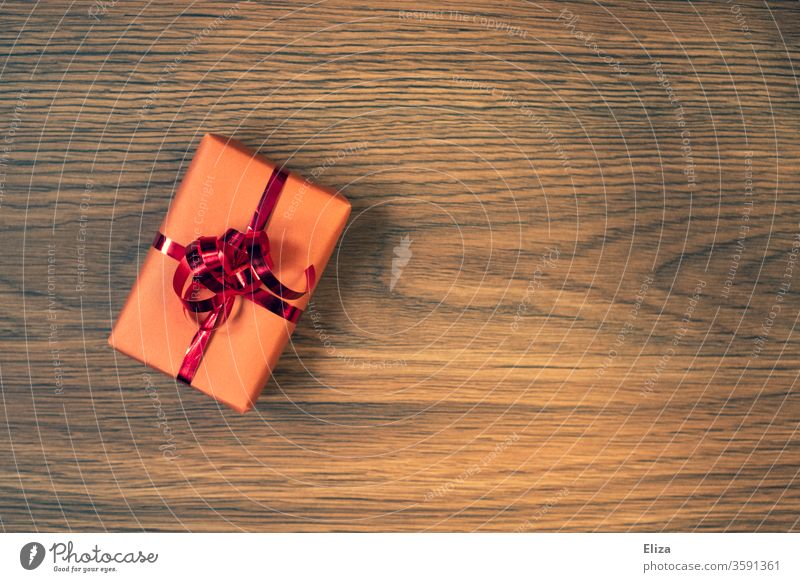 A wrapped gift with a red ribbon on a wooden background Gift Packaging Gift wrapping Birthday Christmas Christmas gift Birthday gift Red Pink Wood Anticipation