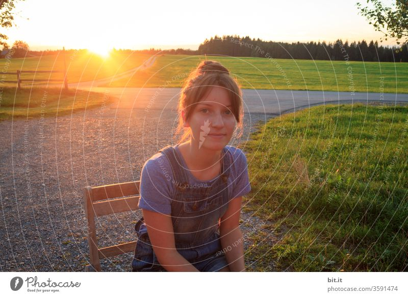 Teenager sitting on a path with pebbles, on a wooden chair at sunset, looking into the camera. Teenager enjoys sitting in the evening sun, on a summer holiday in the countryside, in front of green landscape, meadows, pasture, forest and warm sunlight.