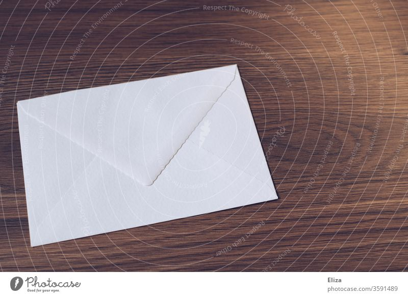 White envelope on a wooden table. Writing letters. Mail. Envelope (Mail) Letter (Mail) Communicate Paper Transmit Wood Table Wooden table Write Brown Mailing