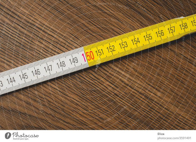 Scale of a meter rule. 150 cm or 1.5 meter distance. Social Distancing. Distance rules. gap Meter rule scale keep sb./sth. apart social distancing wood measure