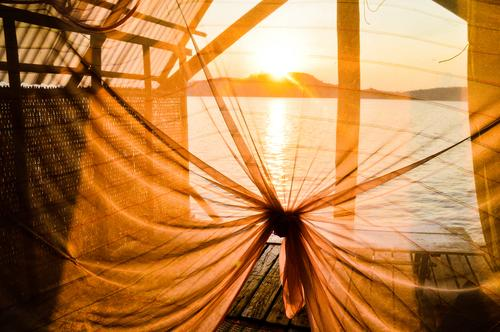 Sunset light shining thru a silk canopy inside a summer bungalow in Koh Sdach island or King's Island located in Cambodia at the Gulf of Thailand koh sdach