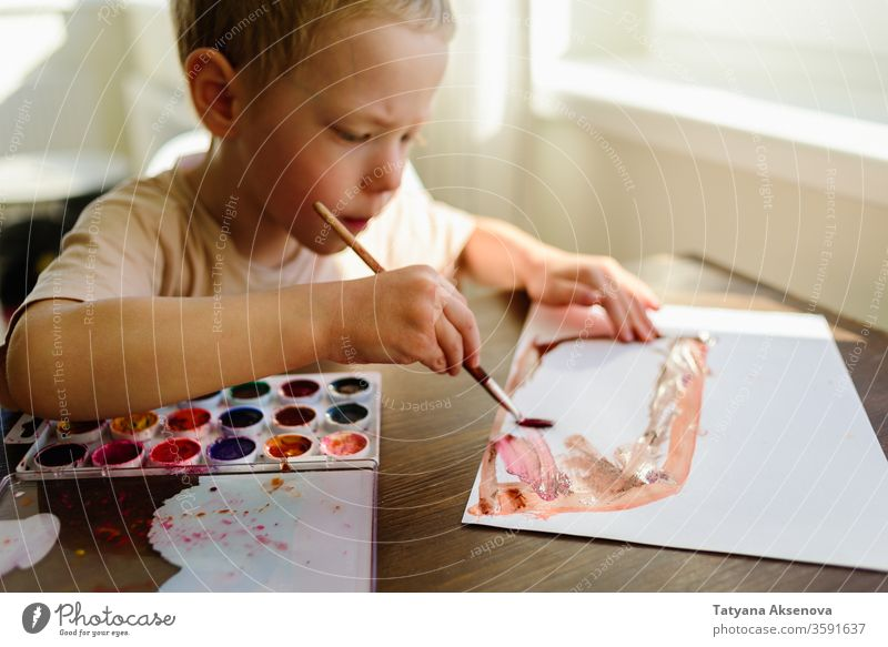 Child drawing in watercolor very enthusiastically child boy art home morning sunny childhood kid education creative little creativity preschooler caucasian