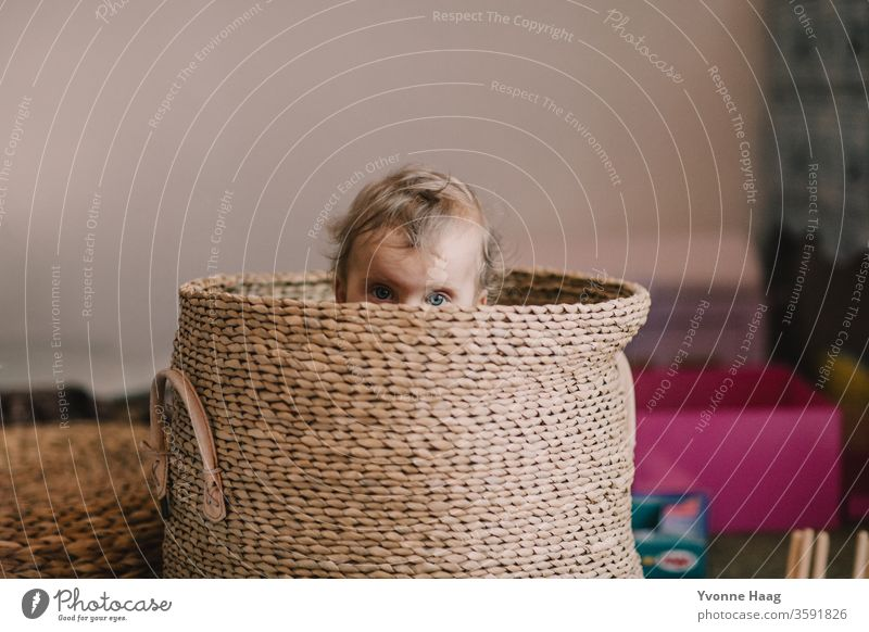 Baby eyes looking out of a basket laughing child Laughter little child little boy little girl Brilliant hiding Hide Relaxation Parenting Childhood memory