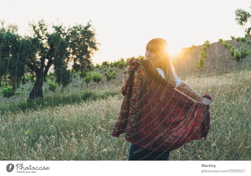 Portrait of a beautiful smiling girl enjoying in nature with a sarong in a field at sunset. woman summer lifestyles sunny young happy grass romantic dreams