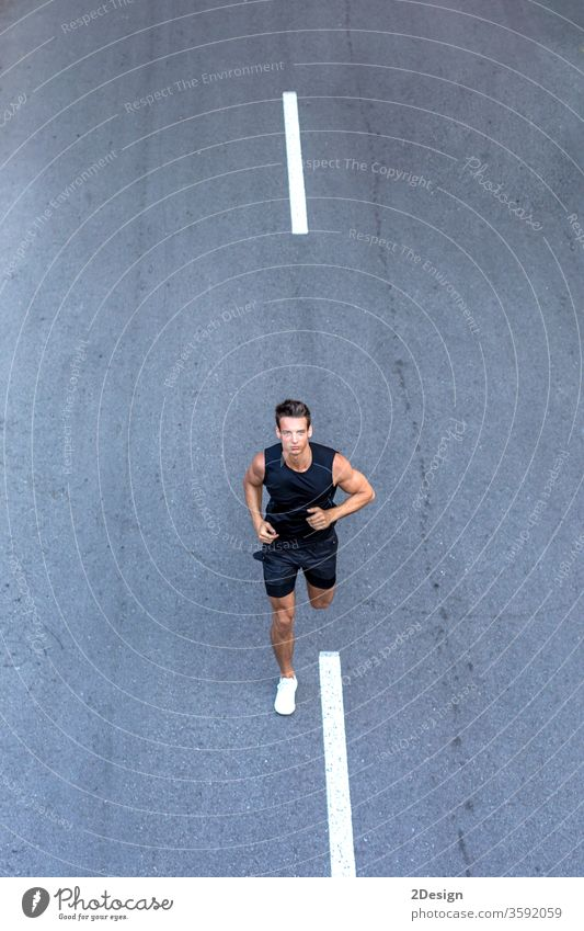 Top view athlete runner training at road in black sportswear. man adult jogging lifestyle athletic sporty exercise young active healthy summer activewear fit