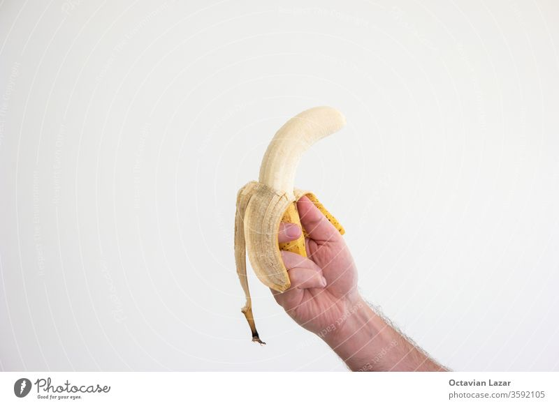 Caucasian male holding a ripe spotted banana in his hand isolated on white palm fresh diet offer snack give gestures natural organic tropical sweet fruit yellow