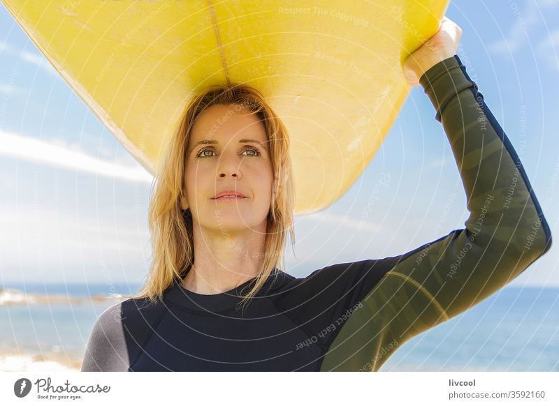 surf woman with yellow board on her arms on the french coast surfer blonde lifestyle people one person human sport adult portrait outdoors scene sky sea