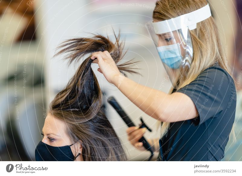 Hairdresser, protected by a mask, combing her client's hair with a hair iron in a salon. woman waves hairdresser girl hairstyle care female beauty treatment