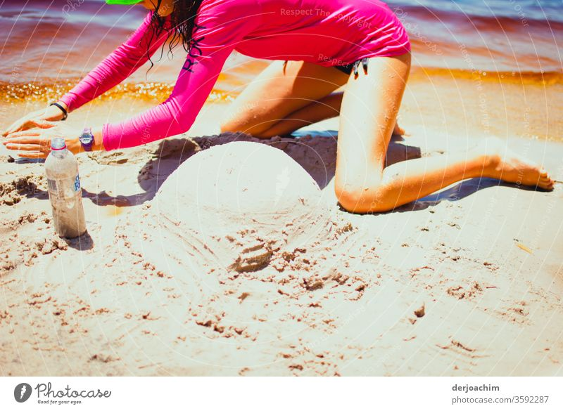 In the hot sand an Australia snowman is to be built. A girl in a red swimsuit at the water has already formed a small round hill. Sand Summer Beach Ocean Water