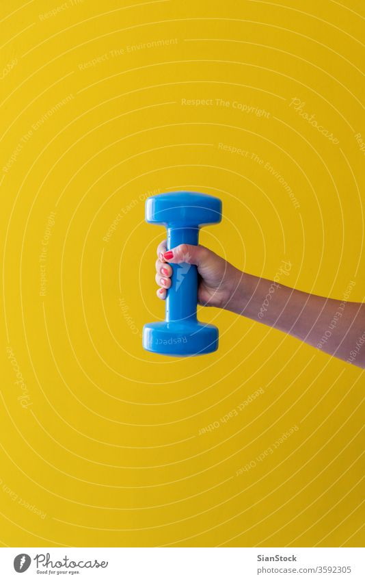 Womans hand holds a dumbbell on a yellow background activity style grab holding nails red lifestyle physical arm heavy concept isolated bodybuilding object