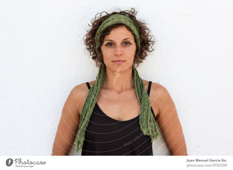 A curly caucasian brunette female with a green hairband standing in front of a white wall with hands behind the back woman person young adult beauty isolated