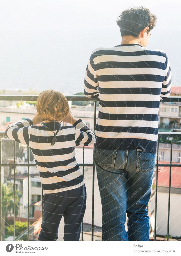 Father and son wearing striped shirts father fathers day authentic together caucasian family love boy kid city balcony celebrate candid real look urban watch