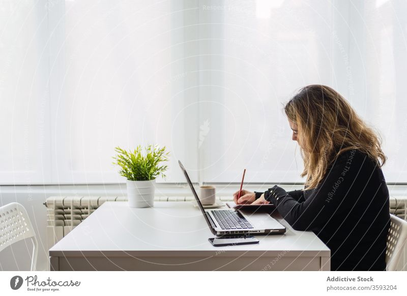 Young woman working with laptop at home take note online remote table casual busy young female workplace freelance device gadget internet write notebook modern