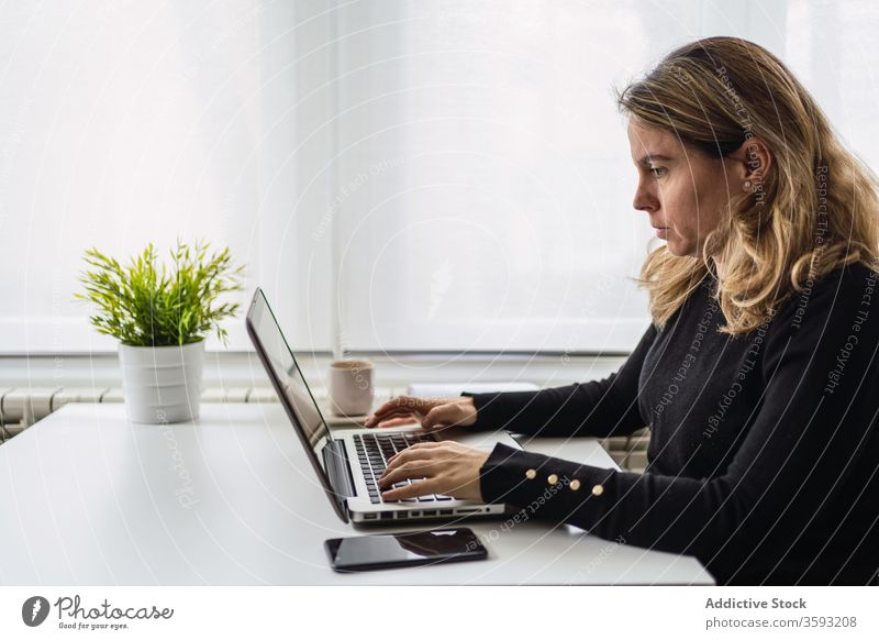 Young woman working with laptop at home online remote table casual busy young female workplace freelance device gadget internet write notebook modern job focus
