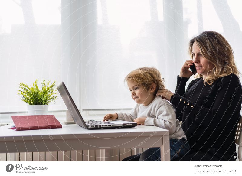 Woman with little kid working on laptop at home woman mother using together online busy remote child curious point motherhood interact parent female
