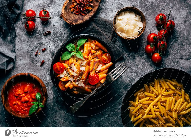 Appetizing penne with arrabiata sauce and fresh tomatoes on table pasta gastronomy ingredient parmesan italian tradition basil food bunch product sun dried meal