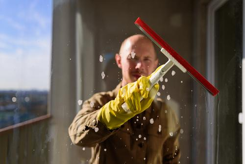 Man washing window in yellow rubber gloves cleaner domestic work glass squeegee housework water person hygiene home transparent household service detergent hand