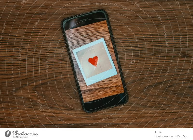 A photo with a heart on the screen of a smartphone. Online dating. Tinder. Communication. Heart Love Screen display Polaroid symbol communication Emotions Chat