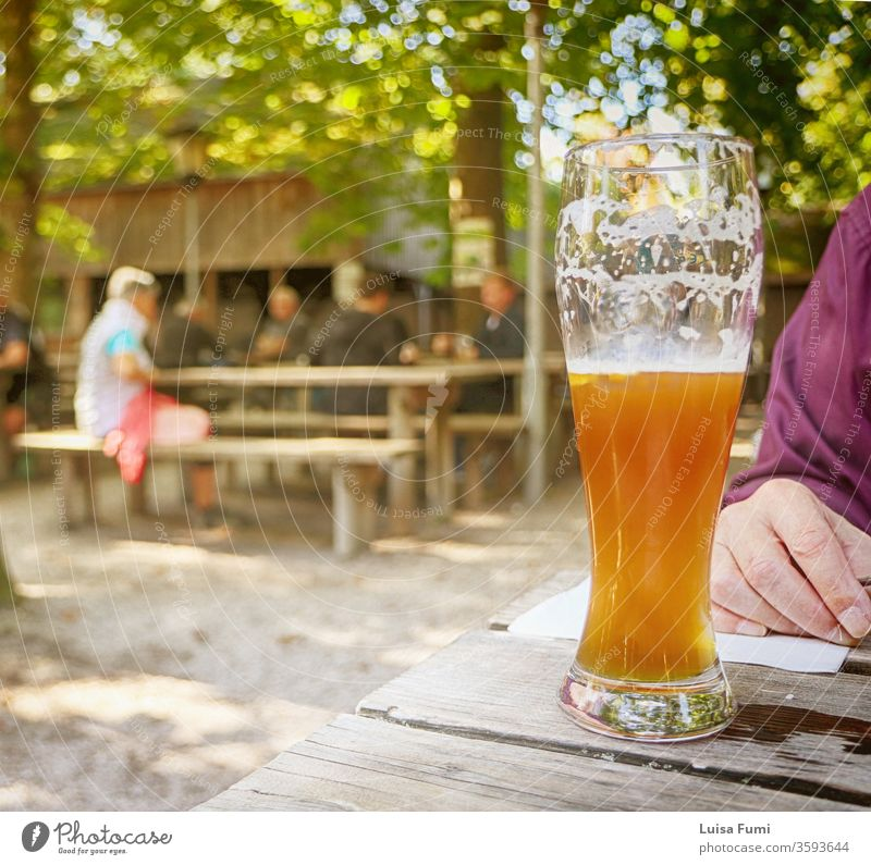 Glass of Bavarian beer at beer garden, blurred background typical drink glass froth open air seasonal restaurant local specialties summer spring food outdoors