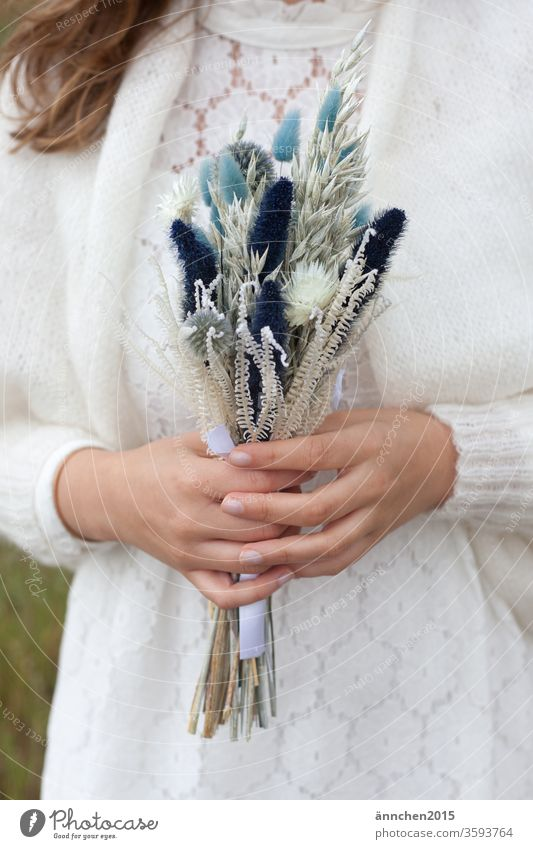A woman, it could be a bride, holding a bouquet of dried flowers Ostrich Dried flowers Bride Wedding Firm celebration get married hands White white dress Jacket