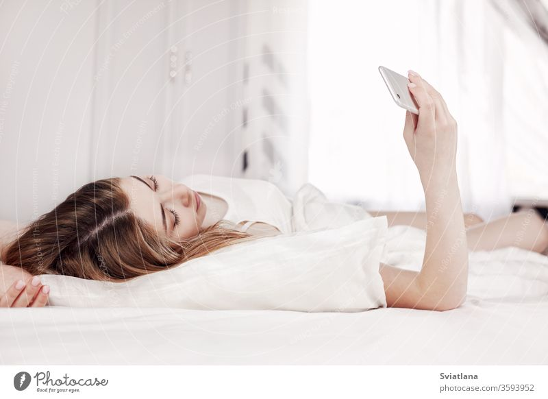 Beautiful young girl looks at the phone while lying on the bed. A girl reads messages on her phone when she wakes up in the morning woman sleeping home pillow