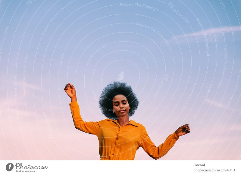 black woman dancing with the wind outdoors blue sky girl young people portrait lifestyle cool lovely garden yellow flower exterior nature afro hair