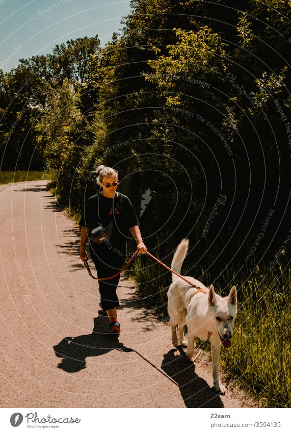 Young woman walks with white sheepdog gassi Walk the dog Dog Cool Easygoing fashion Fashion youthful teen Shepherd dog White already stroll Nature Landscape