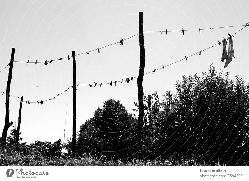 Clothesline with clothespins and posts as a black and white silhouette against the sky Clothes peg Laundry Washing day Dry Clean Pole Household