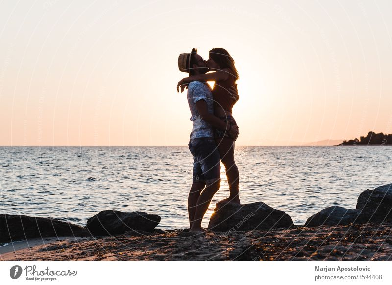 Young couple kissing on the beach in sunset young man woman love sea ocean honeymoon lovers newlyweds romance romantic casual travel holiday summer coastline