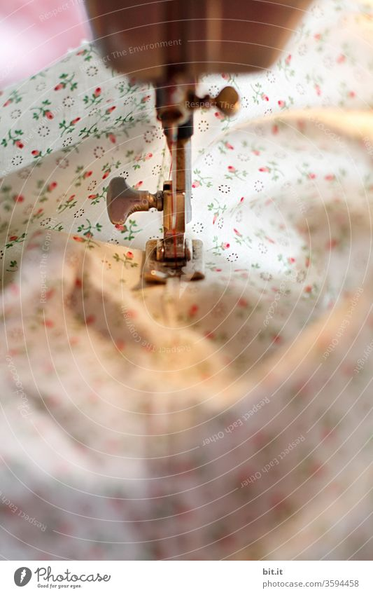 Detailed view of sewing machine foot, quilting foot sewing, quilting the floral fabric. Bright, white sewing work with cotton fabric in the light of the sewing machine. Work, gainful employment in the tailor craft in tailoring, workshop, sewing room, studio, sewing shop, factory.
