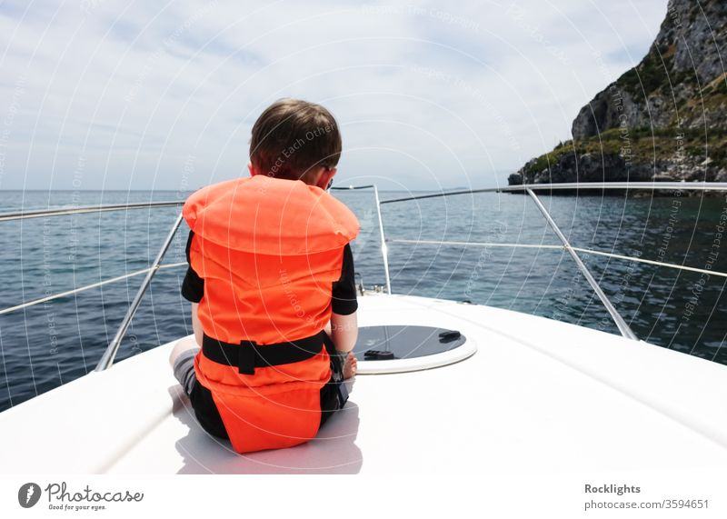 Rear view of a young boy sitting on the deck of a motor boat and wearing an orange life jacket Boy child rear view motorboat buoyancy aid sea at sea facing away