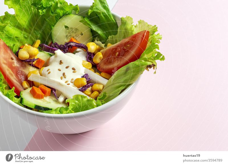 Fresh lettuce salad with tomatoes, red onion, corn, carrots, cucumber food letucce sauce fresh vegetables vegan vegan food healthy food detox diet bowl