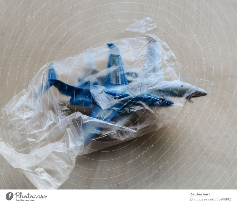 Two passenger planes, toys, in a garbage bag as a symbol of the crisis in aviation Airplane Passenger plane Toys Crisis transparent Blue Trash Environment