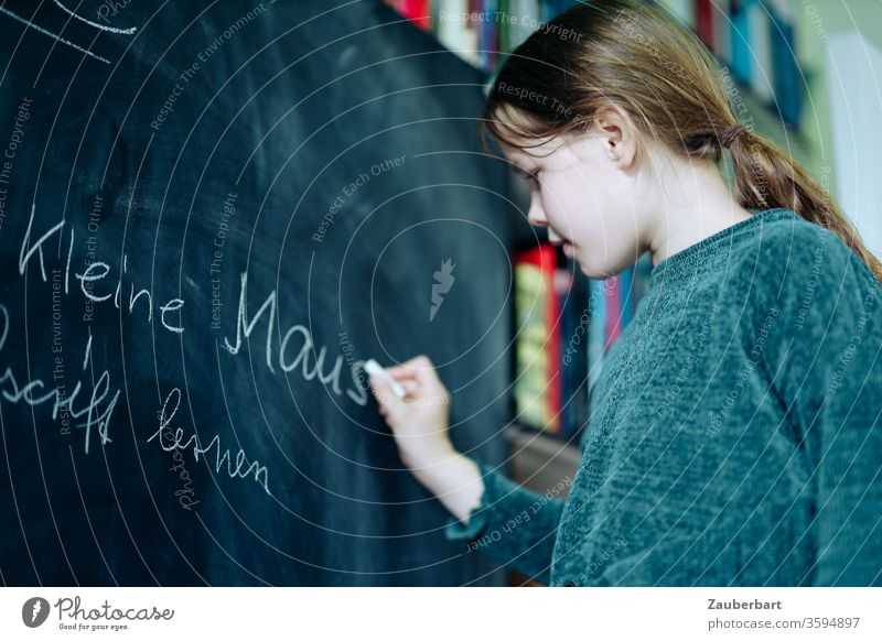 Homeschooling II - Girl writes with chalk on a blackboard a practice set for cursive writing, in the background bookcase School girl pupil schuler