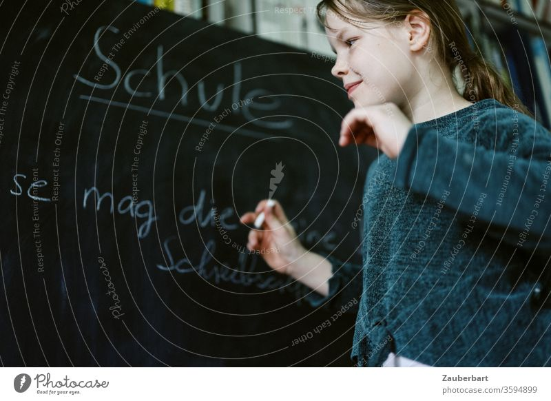 Homeschooling VII - Girl plays school and writes with chalk on a blackboard a practice set for cursive writing, in the background bookcase School girl pupil