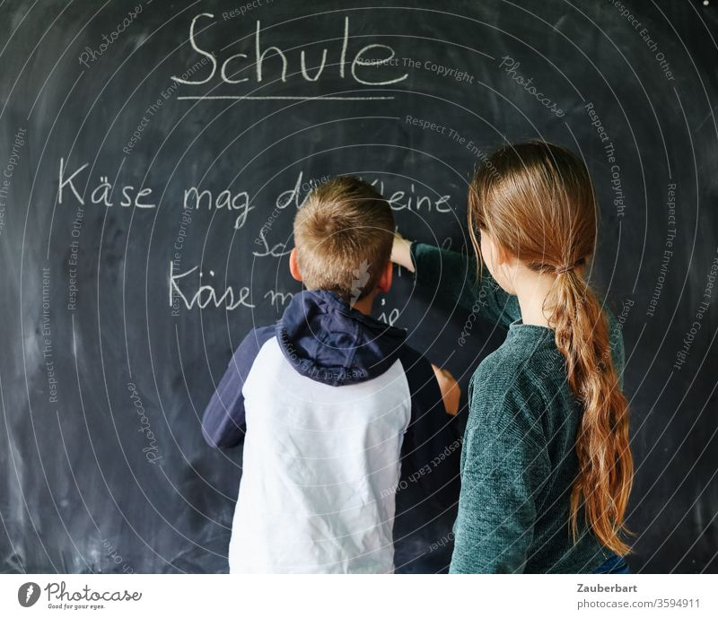 Homeschooling IV - Children play school, one of them writes with chalk on a blackboard a practice sentence for cursive writing School Boy (child) pupil schuler