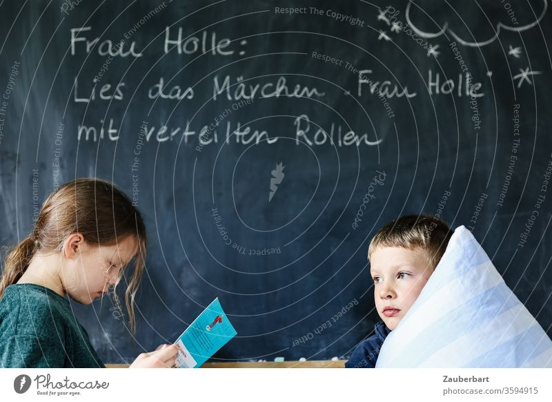 Homeschooling VI - Children read the fairy tale Frau Holle in front of a blackboard with distributed roles, the boy holds a pillow School Mother Holle